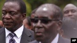 Emmerson Mnangagwa, left, Vice President of Zimbabwe stands next to Zimbabwean President Robert Mugabe after the swearing in ceremony at State House in Harare, Friday, Dec, 12, 2014. (AP Photo/Tsvangirayi Mukwazhi)