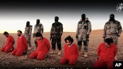 This undated image is taken from video posted online Jan. 3, 2016, by the Islamic State group. The group claims it shows its members executing five men they accuse of spying for Britain in Syria.