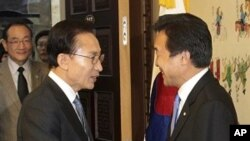 South Korean President Lee Myung-bak, left, shakes hands with Sohn Hak-kyu, chairman of the leading opposition Democratic Party, before their meeting at the National Assembly in Seoul, Noyember15, 2011.