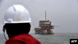 Seorang pekerja memperhatikan anjungan pengeboran gas milik ENI di Laut Adriatik, 6 April 2016.