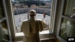 Paus Fransiskus tampak melakukan pemberkatan menghadap ke arah Lapangan Santo Petrus, Vatikan yang kosong tanpa pengunjung karena larangan perjalanan dan keluar rumah di Italia, hari Minggu (15/3).