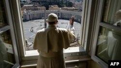 El papa Francisco da la bendición a una vacía Plaza de San Pedro, en un gesto simbólico, luego de pronunciar su sermón dominical del Angelus, el 15 de marzo. Foto de servicio de prensa del Vaticano.