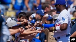 Los Angeles Dodgers' Yasiel Puig signs autographs for fans prior to an opening day baseball game against the San Diego Padres, Monday, April 6, 2015, in Los Angeles. (AP Photo/Mark J. Terrill)