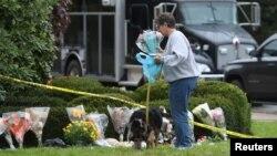 Uma senhora deixa flores num memorial às vítimas do ataque à sinagoga Árvore da Vida, Pittsburgh, Pensilvânia, 28 Outubro, 2018.
