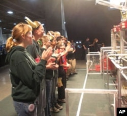 Student competitors watch a match between the soccer-ball kicking robots that they created.