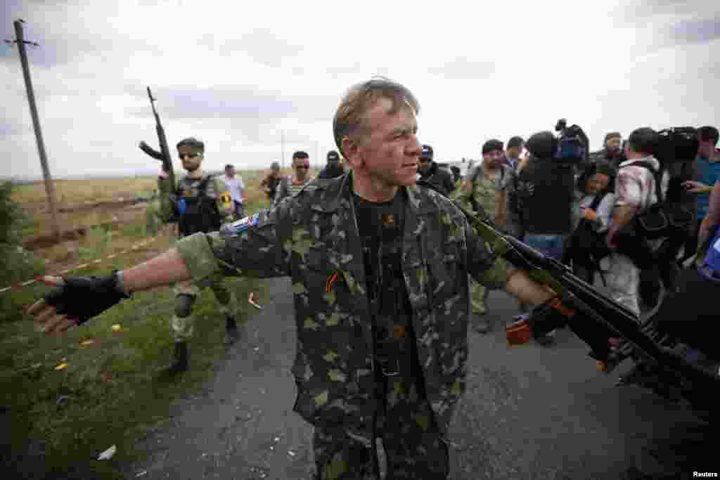 An armed pro-Russian separatist stands guard as OSCE monitors and a team of Malaysian air crash investigators inspect the crash site of Malaysia Airlines Flight MH17, near Hrabove, Ukraine, July 22, 2014.