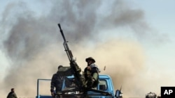 A rebel fighter sits on a truck as he fires an anti-aircraft gun during an air strike at a rebel fighters checkpoint in Al Ugaila area along a road between the towns of Brega and Ras Lanuf, March 12, 2011