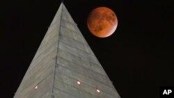 La llamada Luna sangrienta pasa detrás del pico del obelisco dedicado a George Washington, en la capital estadounidense.