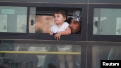 A Syrian man with a child is shown in a bus in Jroud Arsal, Lebanon, Aug. 2, 2017.