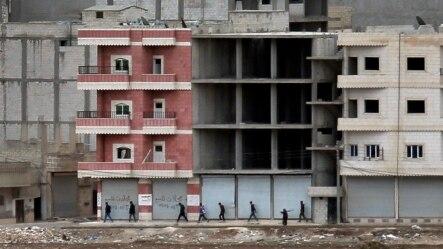 Kobani'de mevzilerine yürüyen Kürt milisler