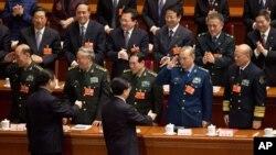 2013年3月14日,卸任的中国党政军领导人胡锦涛和接任的习近平进入北京人民大会堂参加人大会议时一道接受军队代表团的致意。