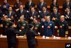 2013年3月14日,卸任的中国党政军领导人胡锦涛和接任的习近平进入北京人民大会堂参加人大会议时一道接受军队代表团的致意