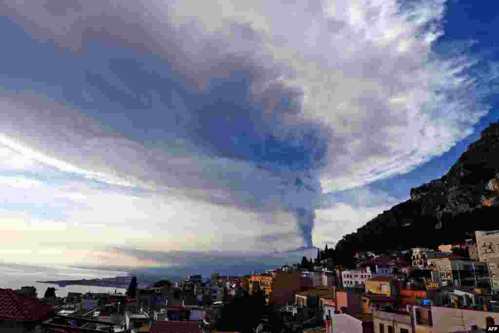 Smoke rises over the city of Taormina, Italy, during an eruption of the Mt. Etna, one of the most active volcanoes in the world, near Catania.