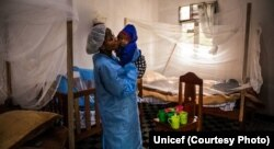 Seorang asisten perawat sedang merawat bayi di Pusat Perawatan Ebola di Butembo, 13 Agustus 2019. (Unicef)