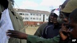 Para pemilih membaca pengumuman yang dipasang di luar sebuah TPS di Harare, Kamis (1/8).