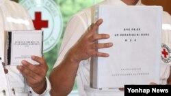 13일 서울 대한적십자사에서 적십자 관계자들이 추석 이산가족 남측 상봉 후보자 가족의 생사확인 결과가 담긴 회보서를 들어보이고 있다.