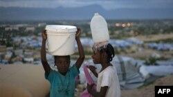 Гаитянские девочки несут воду в семейную палатку в лагере Карадо в Порт-о-Пренсе.