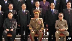 In this undated photo released on Thursday, Sept. 30, 2010, by Korean Central News Agency, North Korean Leader Kim Jong Il, right, poses for a group photo with newly elected members of the central leadership body of the Workers Party of Korea and the part
