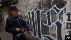 Un policía salvadoreño camina frente a un símbolo de la Mara Salvatrucha, en San Salvador.
