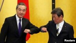 Ngoại trưởng Trung quốc Vương Nghị (trái) chào hỏi vị tương nhiệm Nhật Bản, Ngoại trưởng Toshimitsu Motegi trước cuộc hội đàm ngày 24/11/2020 tại Tokyo. REUTERS/Issei Kato/Pool