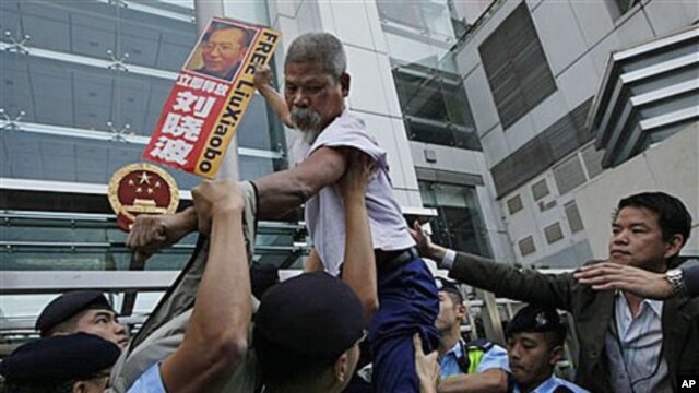 A pro-democracy protester holding the picture of the jailed Chinese dissident Liu Xiaobo, tries to climb across the police line during a demonstration at the China Liaison Office in Hong Kong, Nov 11, 2010 (file photo)
