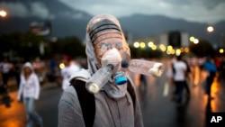 2014年2月18日,在委内瑞拉的加拉加斯市面带塑料水瓶做的防毒面具反对派抗议人士设法阻挡通往机场的道路。
