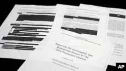 Four pages of the Mueller Report lay on a witness table in the House Intelligence Committee hearing room on Capitol Hill, in Washington, Thursday, April 18, 2019. (AP Photo/Cliff Owen)