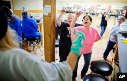 Jackie Suelflow, right, and Mikey Clanton, left, dance and sing during a ladies bowling night in Prairie du Chien, Wis., Wednesday, Jan. 18, 2017.