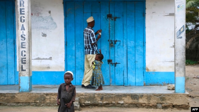 A shop owner closes down his shop on March 7, 2018 in Mocimboa da Praia, Mozambique. Security is increased in the area following attacks from suspected islamists in October.