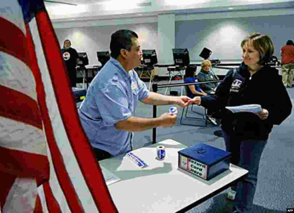 "LAS VEGAS - NOVEMBER 02: Polling place assistant Salvador Cabrera (L) gives an ""I Voted"" sticker to Debbie Cluff after she voted at the Sahara West Library November 2, 2010 in Las Vegas, Nevada. In one of the nation's most closely watched races, U.S. Sena"