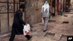 FILE - Аn Orthodox Jew walks behind a Palestinian man on a street in the walled Old City of Jerusalem.