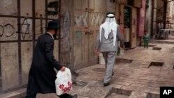 یک مرد یهودی پشت سر یک مرد فلسطینی در بخش قدیمی اورشلیم راه می رود.