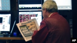 A trader on the floor of the New York Stock Exchange looks at the front page of a newspaper the day after Presiden Obama was re-elected, November 7, 2012.