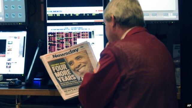 Một nhà giao dịch làm việc tại Sàn giao dịch Chứng khoán New York đọc nhật báo với bản tin hàng đầu về việc Tổng thống Obama tái đắc cử, 7/11/12