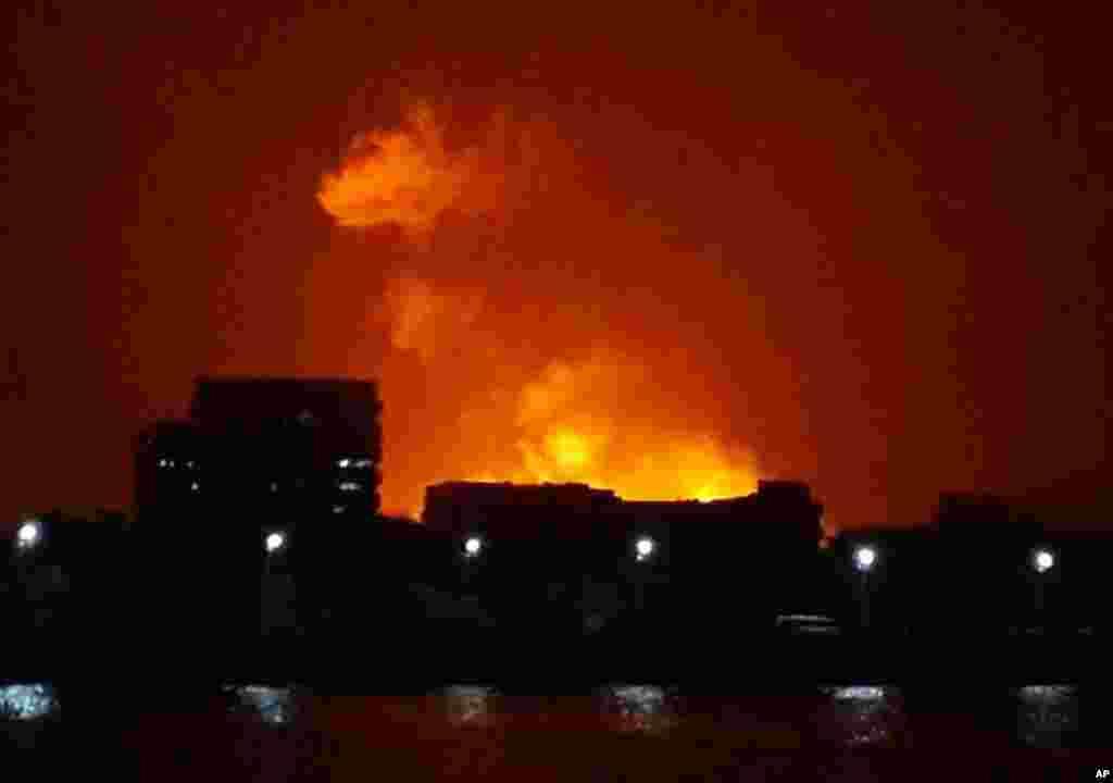 The night sky is lit up as a fire burns aboard the INS Sindhurakshak, an Indian Navy kilo class submarine, Mumbai, August 14, 2013.