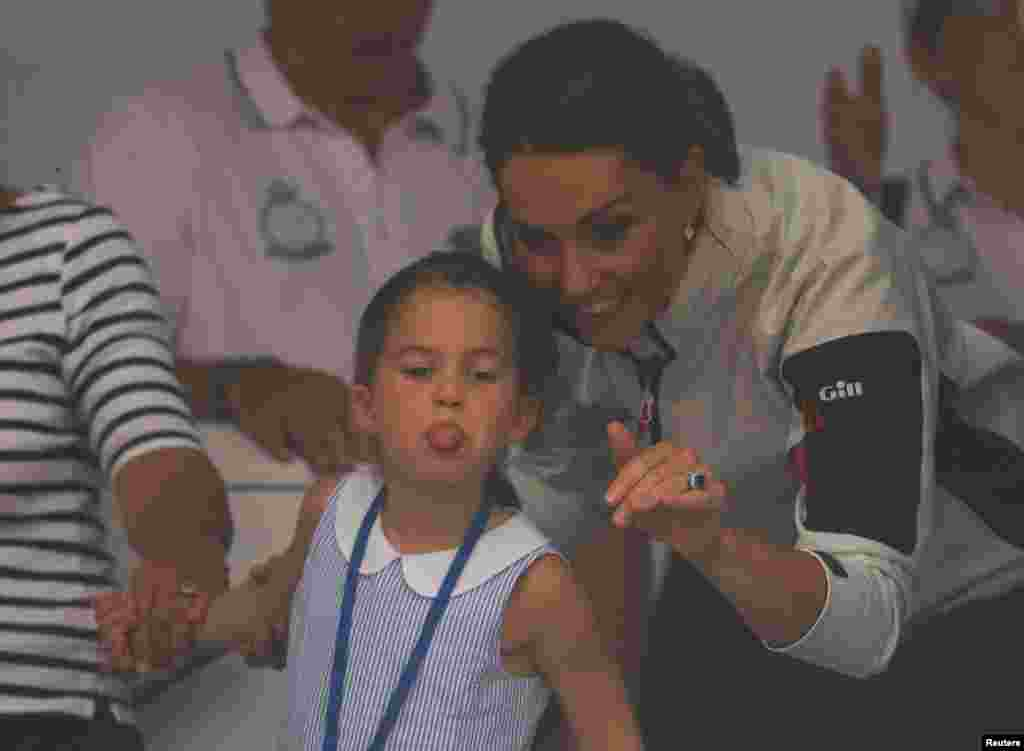 Britain's Princess Charlotte sticks her tongue out next to her mother, Catherine, Duchess of Cambridge, before a presentation ceremony following the King's Cup Regatta in Isle of Wight.