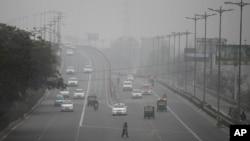 Seorang perempuan India menyeberang jalan raya saat kendaraan bergerak dalam kabut akibat polusi di New Delhi, India (15/1).
