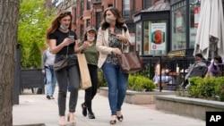 FILE - Pedestrians walk along Boston's fashionable Newbury Street in Massachusetts.