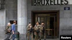 Tiga anggota pasukan keamanan Belgia melakukan patroli di luar stasiun kereta di Brussels, di mana ditemukan paket mencurigakan, Minggu (19/6).