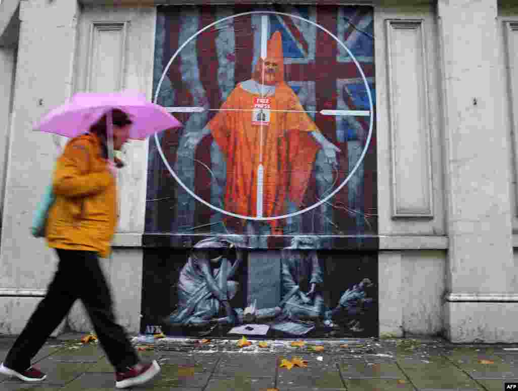 A person passes a graffiti mural of WikiLeaks founder Julian Assange, near Westminster Magistrates Court in London.