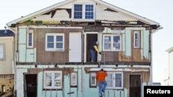 Warga menaiki tangga di luar rumahnya yang hancur karena Badai Sandy di Ortley Beach, New Jersey (7/1). (Reuters/Tom Mihalek)