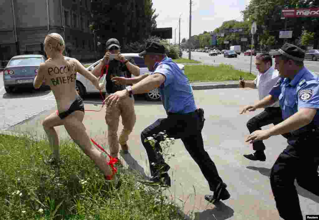 "Ukrainian Interior Ministry officers and a security guard chase an activist from the women's rights group FEMEN, as she stages a demonstration outside the Russian embassy in response to Russian President Vladimir Putin's announcement of his separation from his wife Lyudmila, in Kiev. The words on the woman's back read, ""Push Russia forward!"""