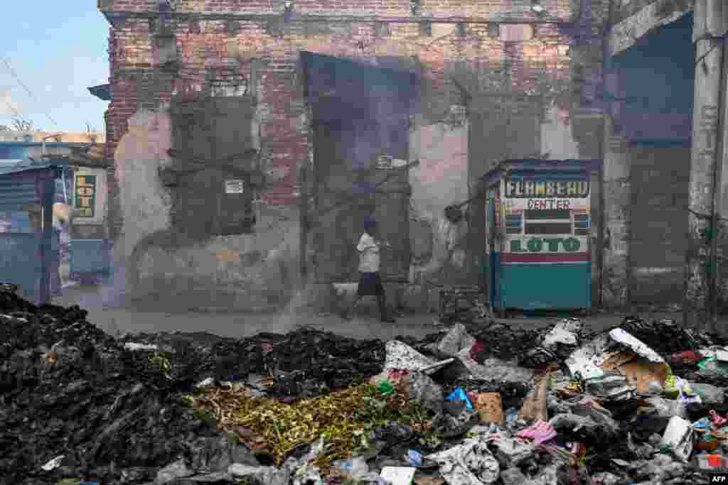 A woman walks past a burning garbage dump in Port-au-Prince, Haiti, Aug. 5, 2019.