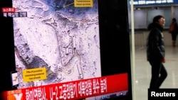 一名旅客2013年2月12日在首爾的一個火車站經過一個正在播放朝鮮核試驗的電視看版。