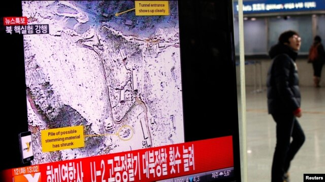 A passenger walks past a television report on North Korea's nuclear test at a railway station in Seoul February 12, 2013.