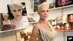 """ARCHIVO- La actriz Brigitte Nielsen muestra su autobiografía, """"You Only Get One Life"""", en la Feria del Libro de Londres. Abril 11, 2011."""