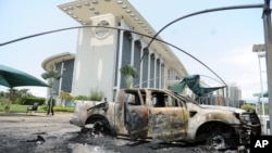 FILE - Burned cars are seen outside a government building, following an election protest in Libreville, Gabon, Sept. 1, 2016.