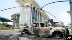 FILE - Burnt-out cars are seen outside a government building, following an election protest in Libreville, Gabon, Sept. 1, 2016.