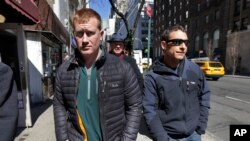 FILE - James Brady (l) and Andrew Rossig (r) two parachutists who jumped from One World Trade Center in September 2013, are accompanied by attorney Timothy Parlatore to surrender to police, in New York, March 24, 2014.