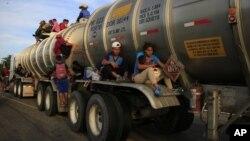 Una mujer con su hijo en brazos viaja sentada en una plataforma sobre la rueda de un camión cisterna, en Niltepec, en el estado de Oaxaca, México, el 30 de octubre de 2018.